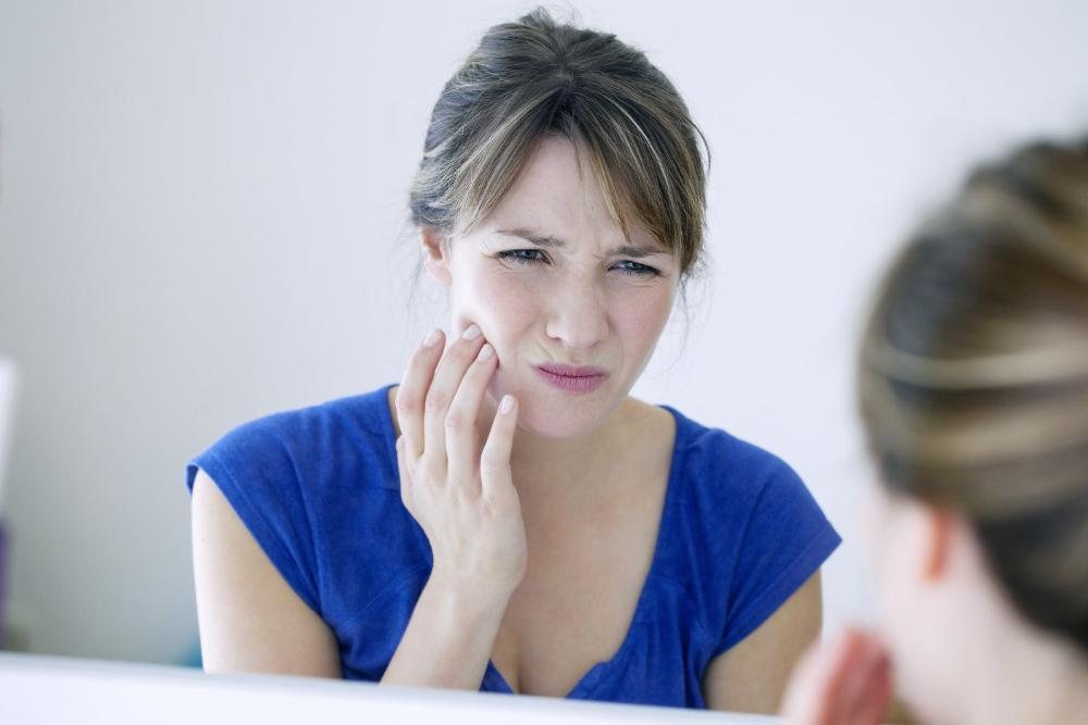 Woman holding jaw from pain | Dentist Highland Park MN
