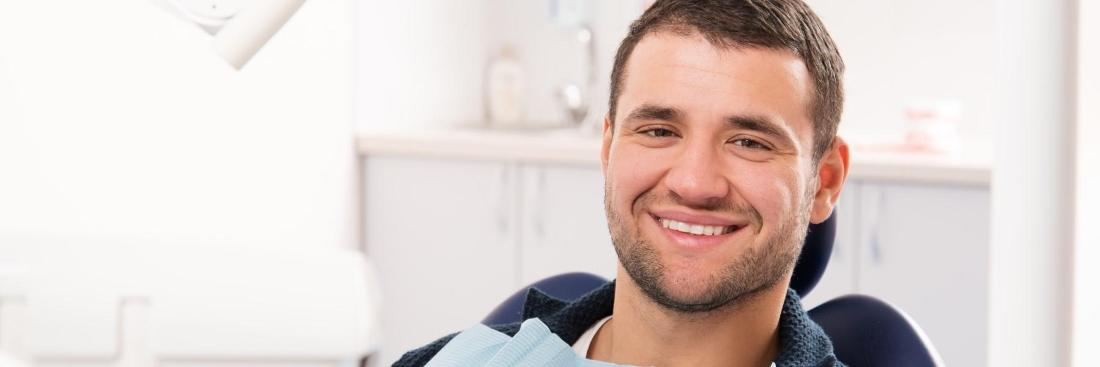 young brown haired male smiling in dentist chair