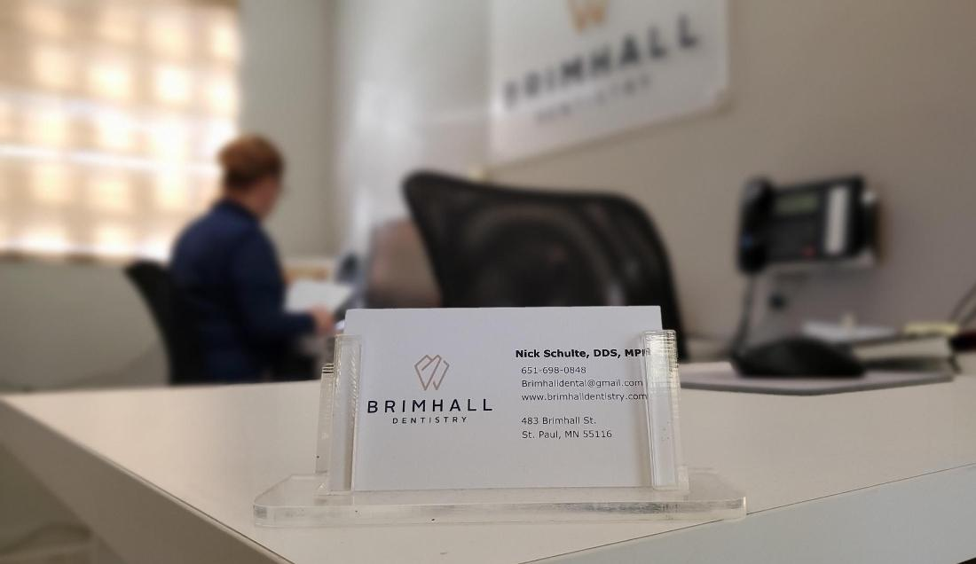 Close up of business cards on welcome desk of Brimhall Dentistry